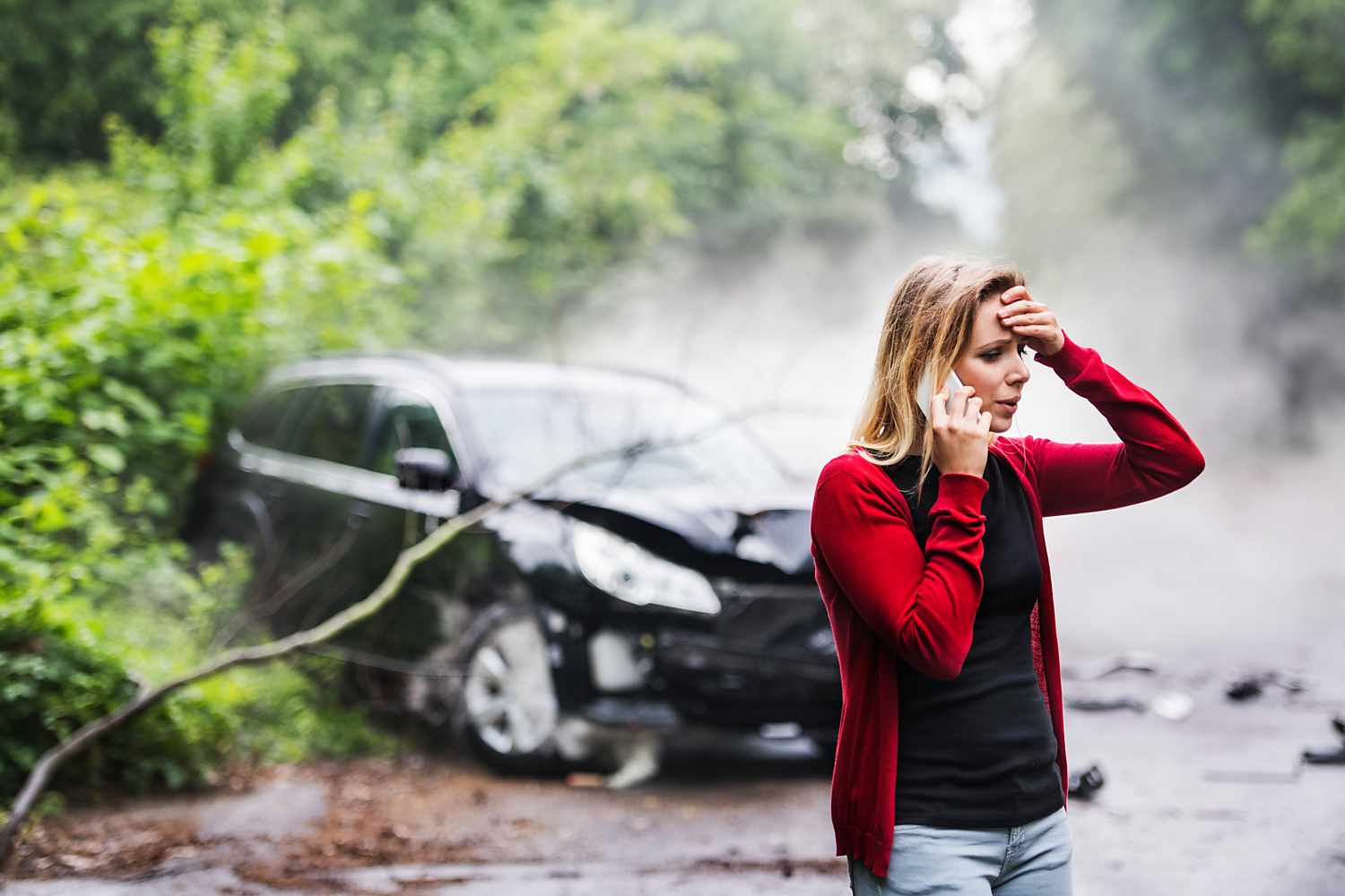 a young woman with smartphone by the damaged car
