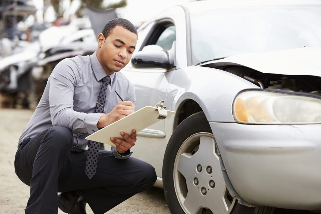loss adjuster inspecting car involved in accident PF3X2KQ